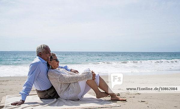 Älteres Ehepaar entspannt sich gemeinsam am Strand und schaut sich die Aussicht an
