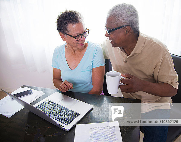 Senior couple sitting at table  using laptop  man holding coffee cup
