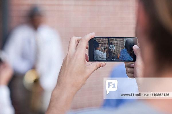Pedestrian taking photograph of street musician  using smart phone