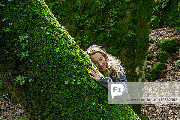 Frau lehnt an moosbedecktem Baum  Spanien