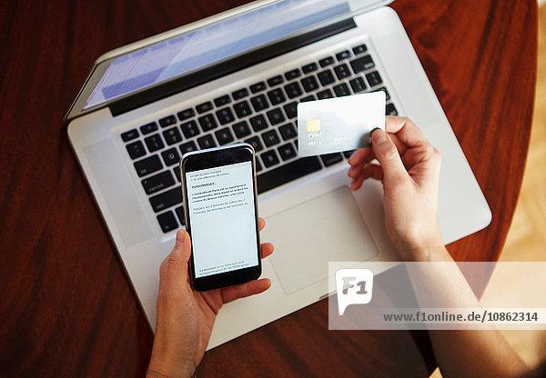 Draufsicht einer Frau mit Laptop  die eine Kreditkarte und ein Smartphone hält