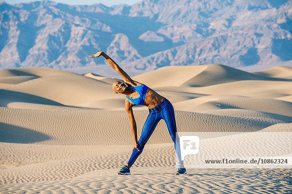 Runner stretching in desert  Death Valley  California  USA