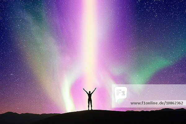 Person stretching arms in front of aurora  Death Valley  California  USA