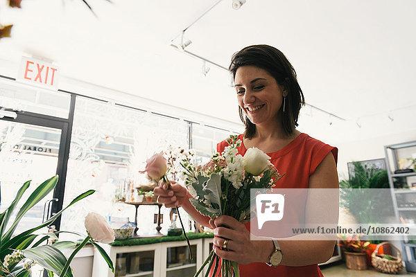 Florist arranging bouquet in flower shop  smiling
