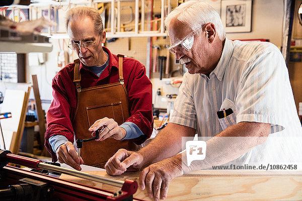 Ältere Männer  die mit der Werkstatt für Tischlereiausrüstung arbeiten