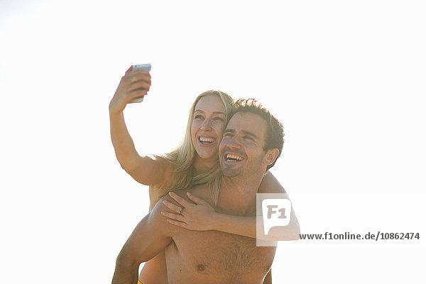 Mann gibt Frau Huckepack mit Smartphone  um sich selbst zu nehmen  lächelnd