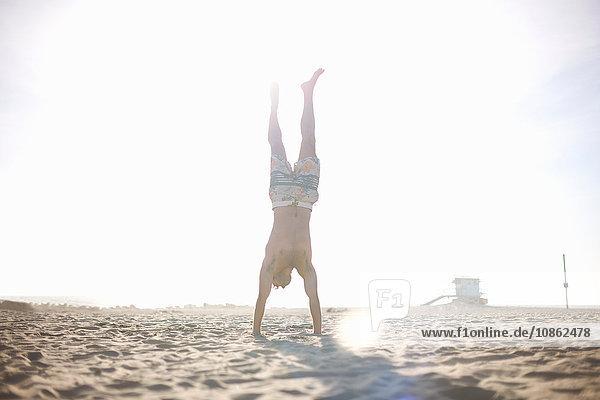 Mittelgroßer erwachsener Mann macht Handstand am Strand