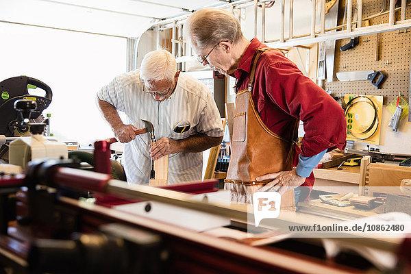 Älterer Mann hämmert Holzblock in Schreinerei