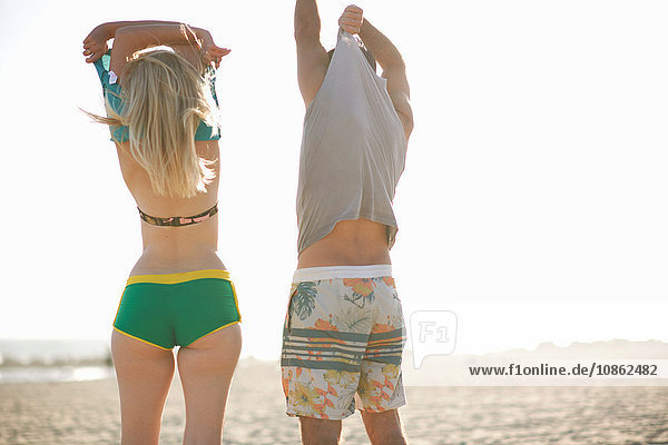 Rear view of couple on beach removing vests