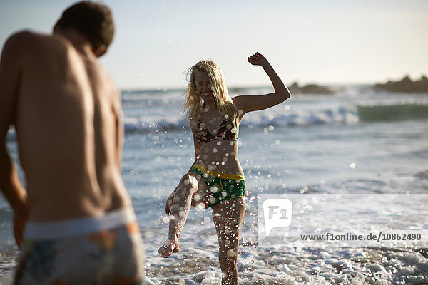 Ehepaar am Strand beim Plantschen im Meer