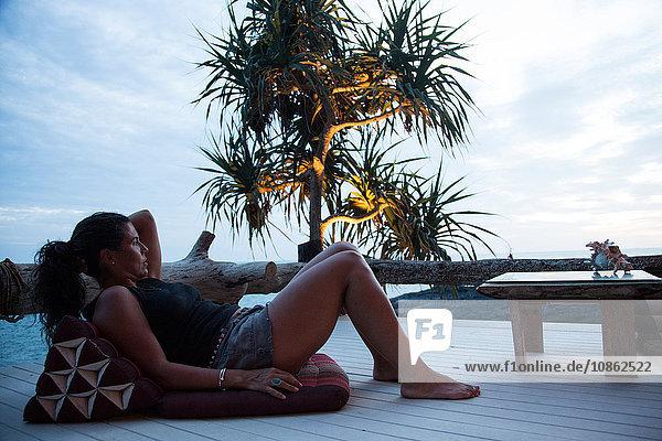 Reife Frau entspannt sich in der Dämmerung auf der Terrasse  mit Blick auf die Aussicht  Koh Lanta  Thailand
