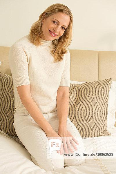 Porträt einer blonden reifen Frau auf dem Bett kniend