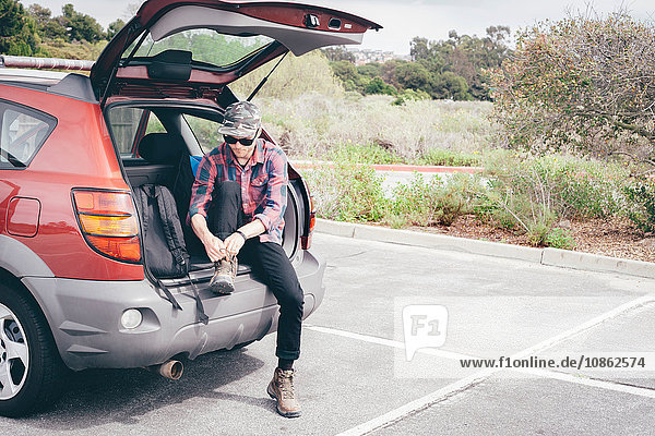 Male hiker sitting on car boot tying hiking boot laces  Crystal Cove State Park  Laguna Beach  California  USA