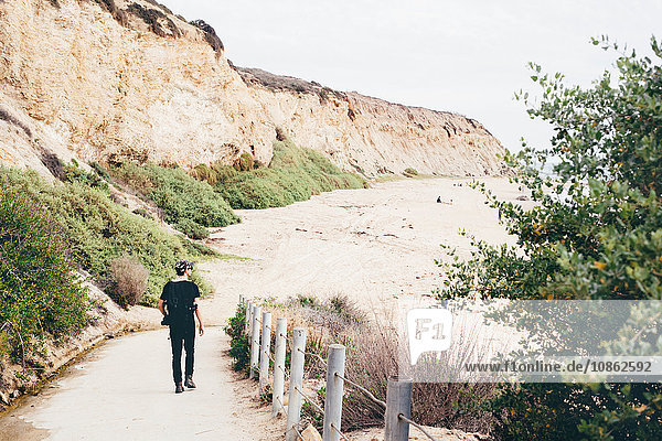 Rear view of male photographer strolling to beach  Crystal Cove State Park  Laguna Beach  California  USA