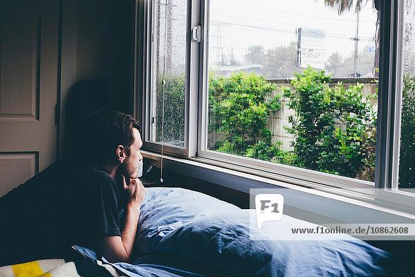 Mann liegt auf Bett und starrt durch Fenster auf Regen