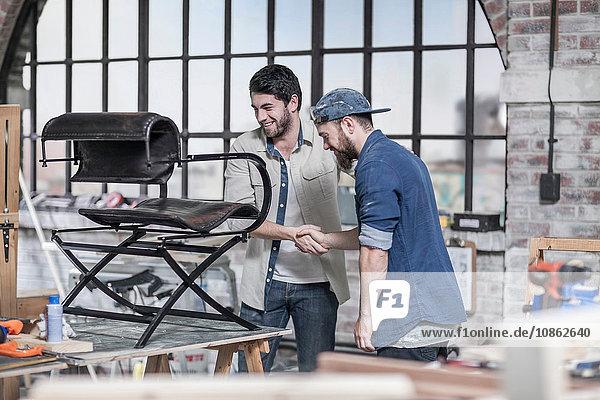Handwerker und Kunde schütteln sich die Hand in einer Restaurierungswerkstatt für Antiquitäten
