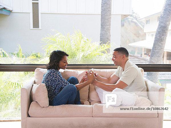 Ehepaar betrachtet Fotos im Smartphone auf dem Sofa