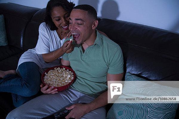 Paar  das mit Popcorn auf dem Sofa fernsieht