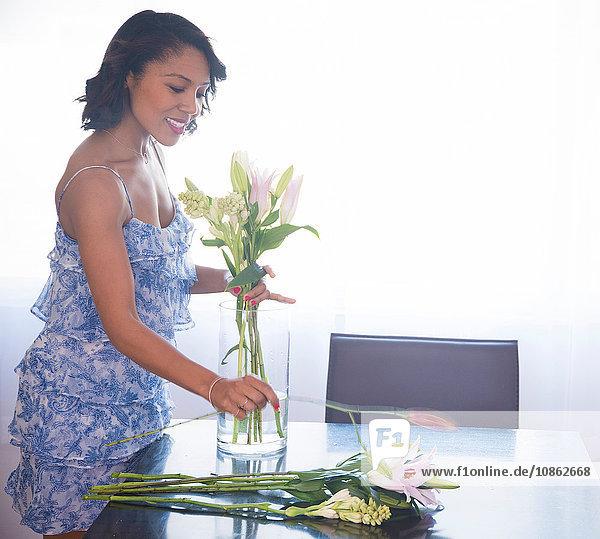Frau arrangiert Blumen in Vase auf dem Tisch