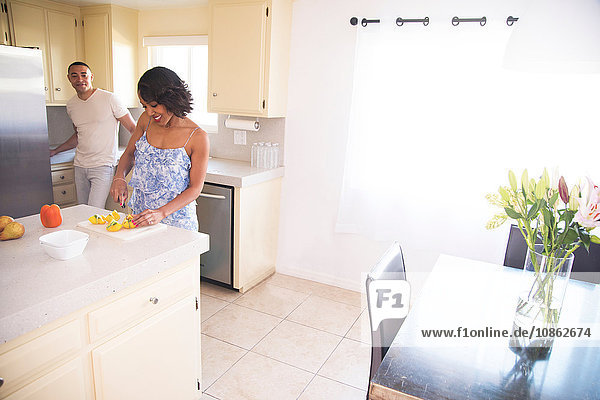 Man chatting with woman cutting fruit in kitchen