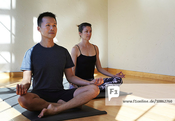 Man and woman doing yoga in studio  in meditation position