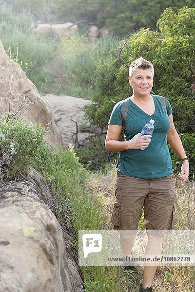 Wanderfrau hält lächelnd eine Plastikflasche