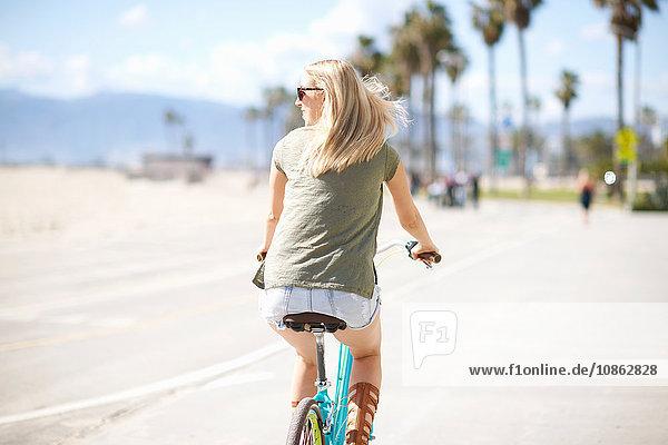 Rückansicht einer jungen Frau beim Radfahren am Venice Beach  Los Angeles  Kalifornien  USA