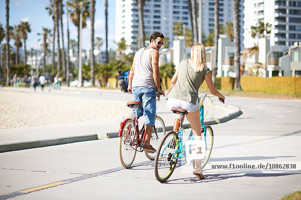 Couple cycling together at Venice Beach  Los Angeles  California  USA