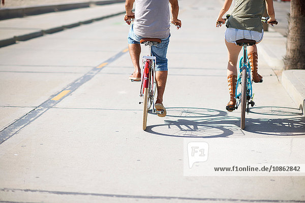 Rear view of couple cycling at Venice Beach  Los Angeles  California  USA