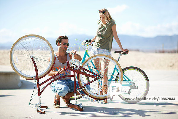 Couple repairing bicycle at Venice Beach  Los Angeles  California  USA