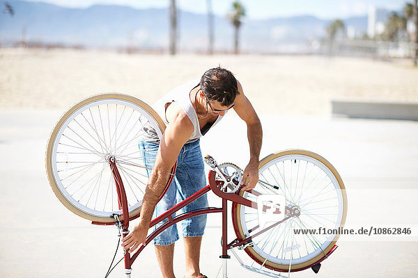 Man repairing bicycle at Venice Beach  Los Angeles  California  USA