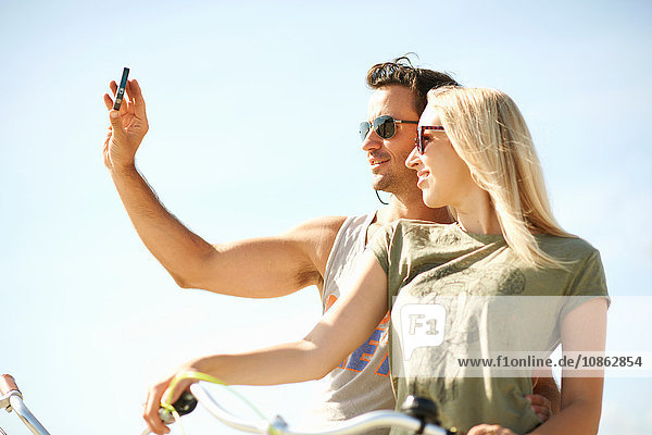 Cycling couple taking smartphone selfie at Venice Beach  Los Angeles  California  USA