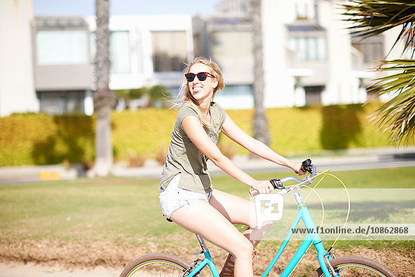 Young woman looking over her shoulder whilst cycling at Venice Beach  Los Angeles  California  USA