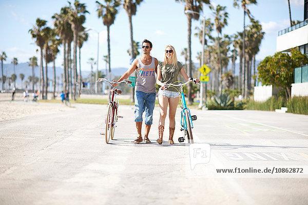 Fahrradfahrerehepaar beim Spaziergang mit dem Fahrrad am Venice Beach  Los Angeles  Kalifornien  USA