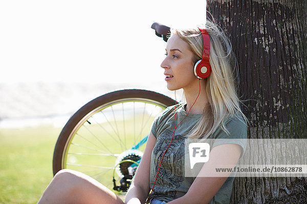 Radfahrerin sitzt am Venice Beach  Los Angeles  Kalifornien  USA  und hört Kopfhörermusik