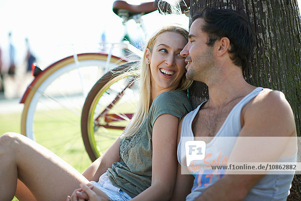 Cycling couple sitting holding hands at Venice Beach  Los Angeles  California  USA