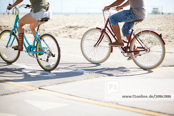 Neck down view of couple cycling at Venice Beach  Los Angeles  California  USA
