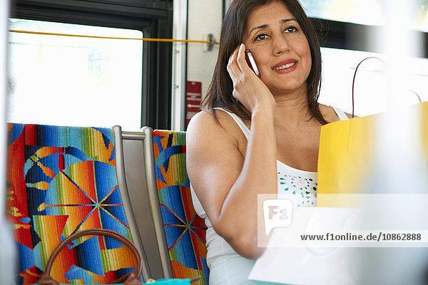 Frau sitzt im Bus und plaudert über Smartphone  Los Angeles  Kalifornien  USA
