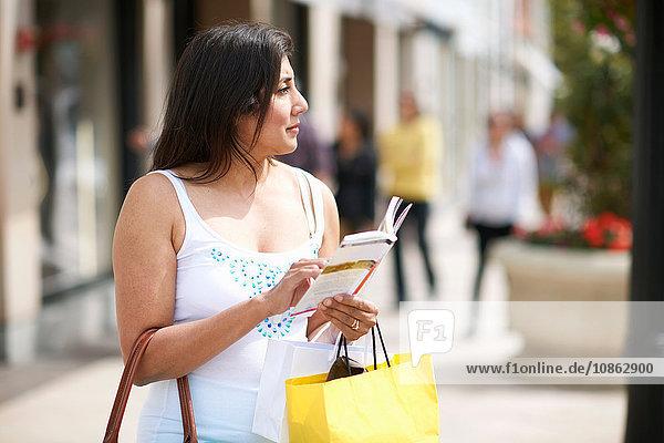 Frau mit Einkaufstasche und Reiseführer