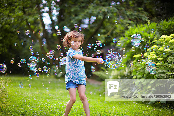 Girl waving bubble wand and making bubbles in garden
