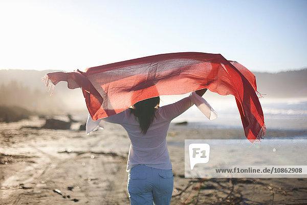 Rückansicht einer Frau  die bei Sonnenuntergang am Strand ein rotes Tuch hochhält  Cresent City  Kalifornien  USA