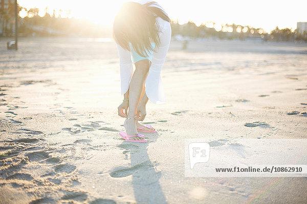 Frau  die sich am Strand von Santa Monica  Cresent City  Kalifornien  USA  bückt  um ihre Fußfessel zu befestigen