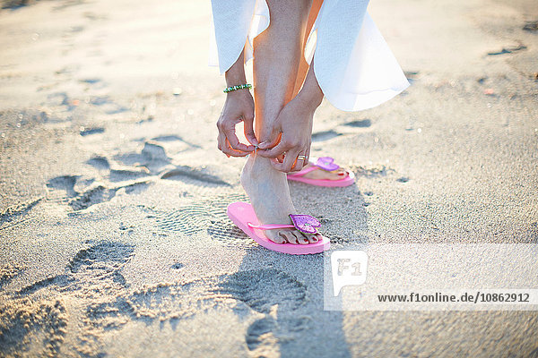 Cropped shot of woman fastening anklet on Santa Monica beach  Cresent City  California  USA
