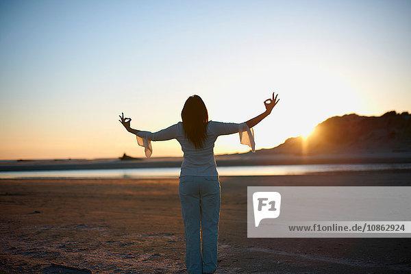 Rückansicht einer Frau mit offenen Armen am Cannon Beach bei Sonnenuntergang  Kalifornien  USA