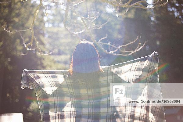 Frau mit kariertem Tuch im Wald