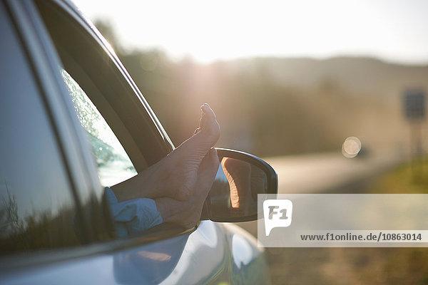 Person ruht mit den Füßen auf dem Fenster des Fahrzeugs