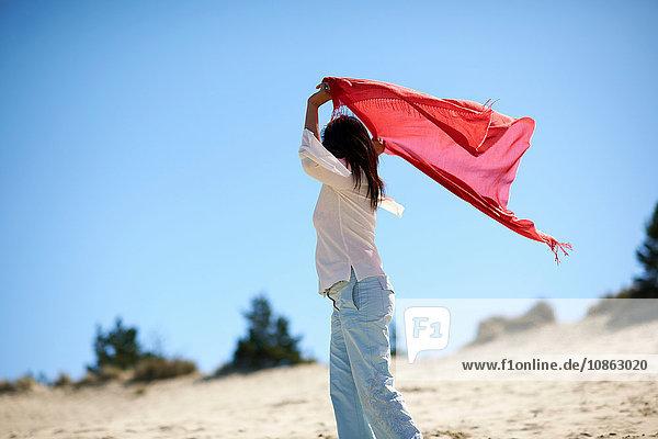 Frau im roten Tuch genießt Strand