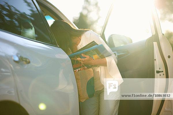 Frau entfernt Habseligkeiten aus dem Fahrzeug