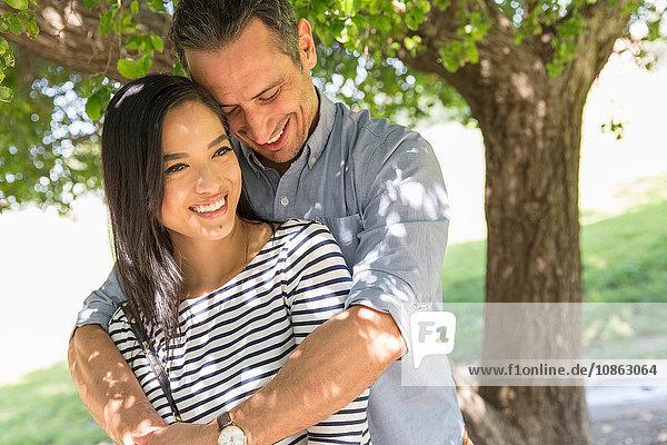 Mann vor dem Baum mit Armen um die lächelnde Frau