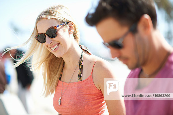 Couple outdoors  wearing sunglasses  smiling  focus on young woman